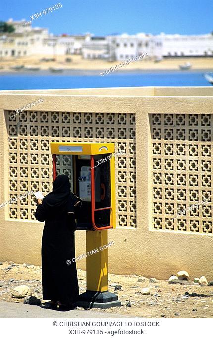 woman black veil dressed and phone box, Sur,Sultanate of Oman,Arabian Peninsula,Asia