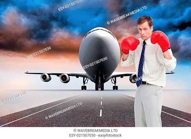Composite image of businessman with his boxing gloves ready to fight