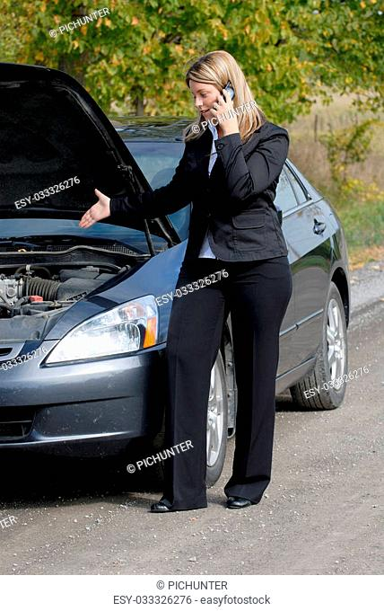 Businesswoman Broken Down By The Side Of The Road With A Stalled Car, Calling For Help On A Cellphone
