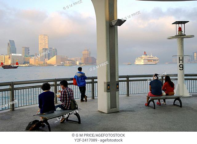 people watch Hong Kong harbour and ships at sunset