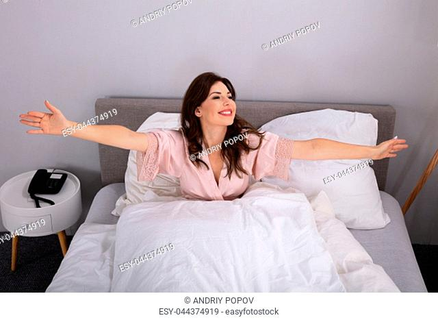 Beautiful Young Woman Stretching Her Arms On Bed In Bedroom