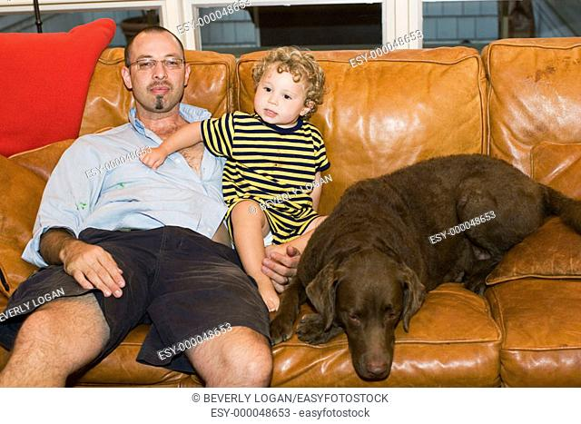 Father, 2 year old boy and dog sitting on a couch