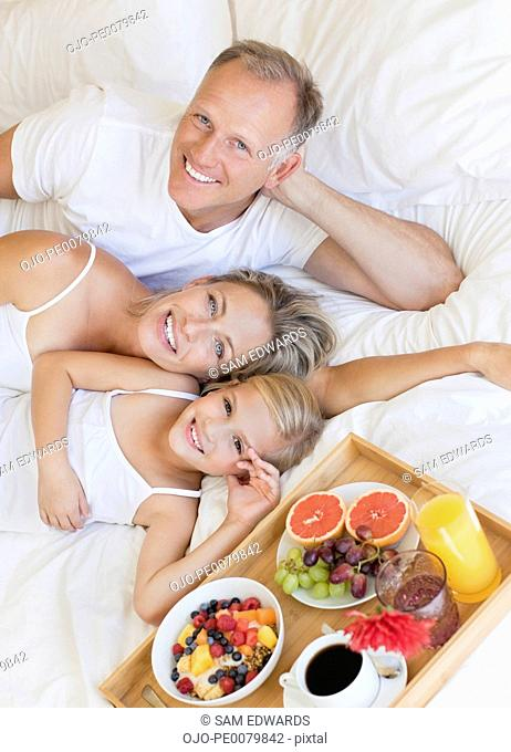 Portrait of smiling parents and daughter laying in bed near breakfast tray