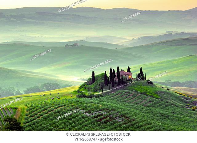 Tuscany, Italy. A beautiful and lonely farmhouse surrounded by green hills of Val d'Orcia