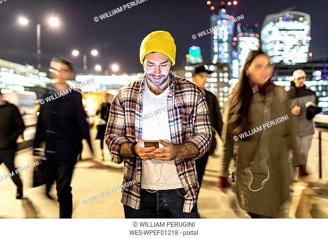 UK, London, smiling man looking at his phone by night with blurred people passing nearby