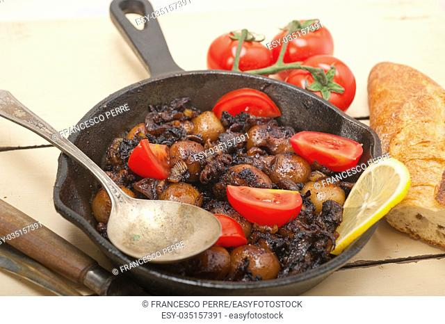 Baby cuttle fish roasted on iron skillet with tomatoes and onions over rustic wood table