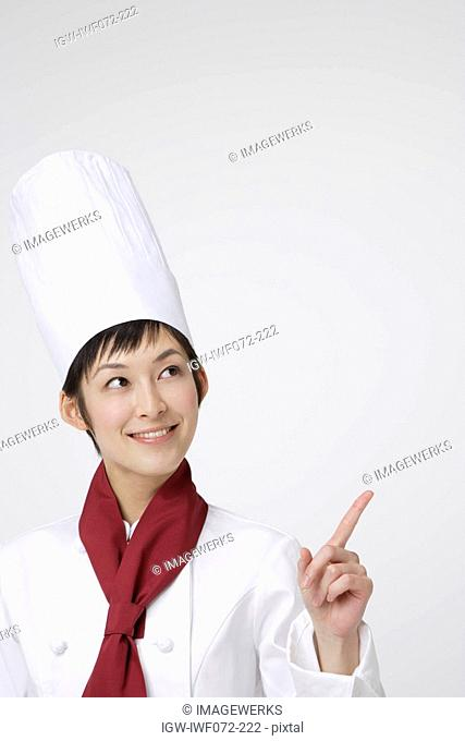 Female chef pointing finger, looking sideways, smiling
