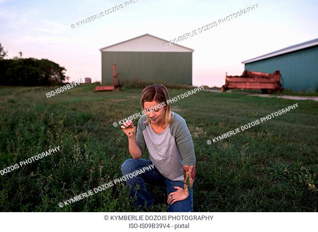 Woman on farm, crouching, smelling plant