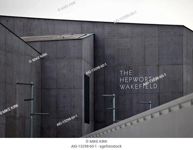 Closeup view of the front elevation and sign over the entrance of The Hepworth Wakefield with the edge of the pedestrian bridge over the River Calder in the...