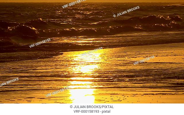 The setting sun reflected in waves as they break on the shoreline
