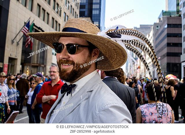 New York, NY - April 16, 2017. A bow-tied man wearing a wide-brimmed straw hat with long sweeping feathers New York's annual Easter Bonnet Parade and Festival...