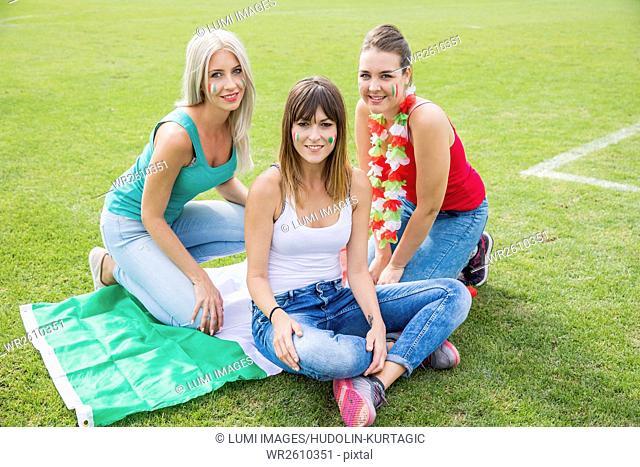 Three female soccer fans sitting on Italian flag