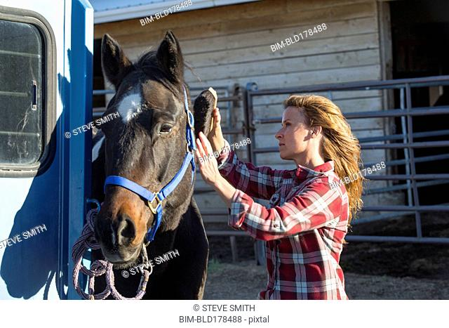 Caucasian woman grooming horse on ranch