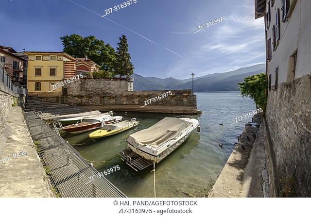 cityscape with boats in small harbor at historical touristic village on Como lake, shot in bright fall light at Urio, Como, Italy