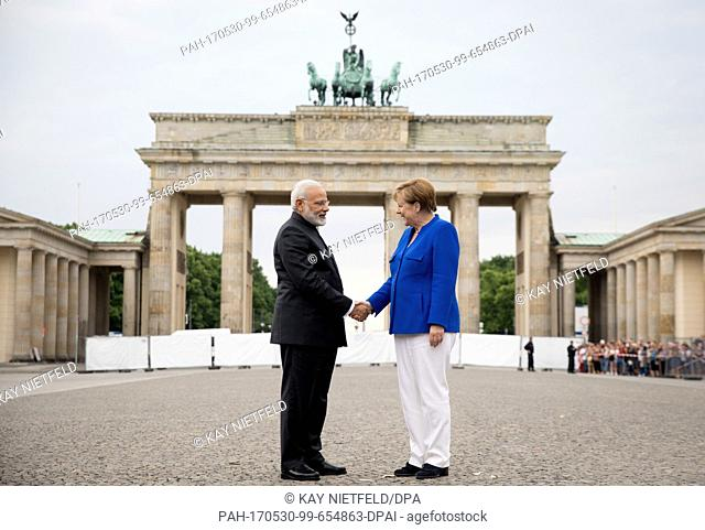 German Chancellor Angela Merkel and Indian Prime Minister Narendra Modi shaking hands on Paris Square in front of the Brandenburg Gate after the German-Indian...