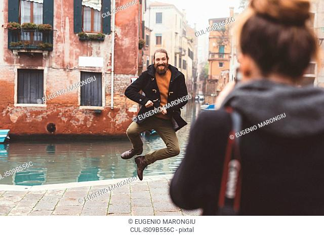 Woman photographing man jumping by canal, Venice, Italy