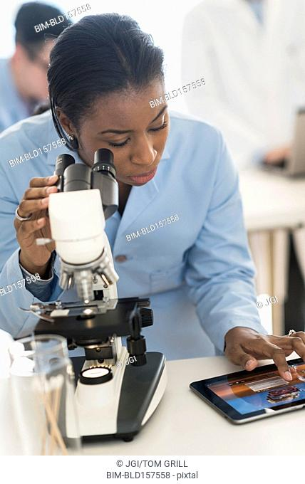 Scientist using microscope and digital tablet in research laboratory