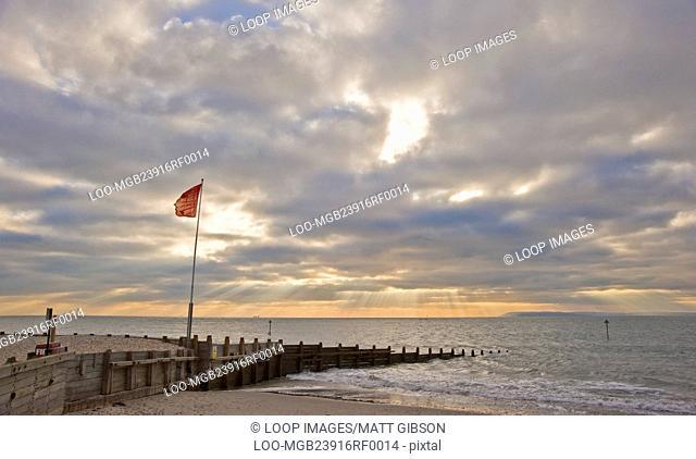 Beautiful inspirational sunset scene with sun beams over smooth sea