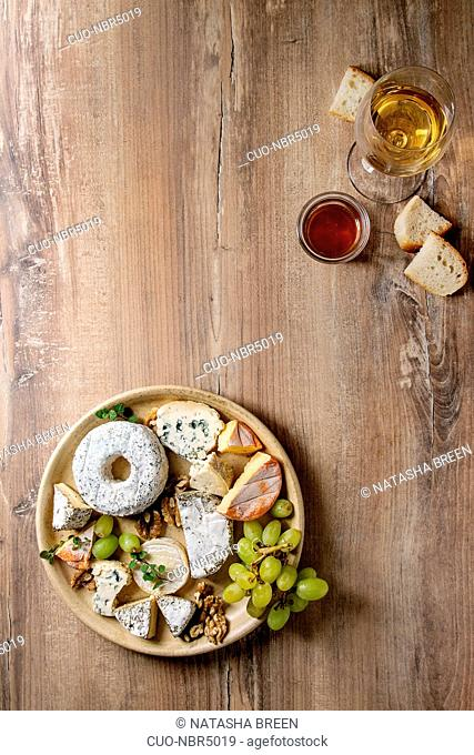 Cheese plate assortment of french cheese served with honey, walnuts, bread and grapes on ceramic plate with glass of white wine over wood texture background