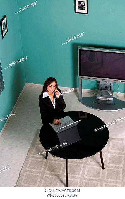Businesswoman with laptop, using cellphone