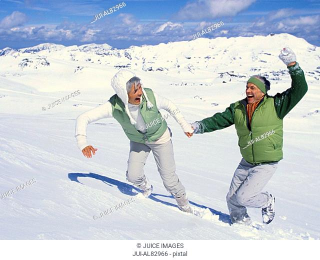 Senior couple holding hands and running in snow