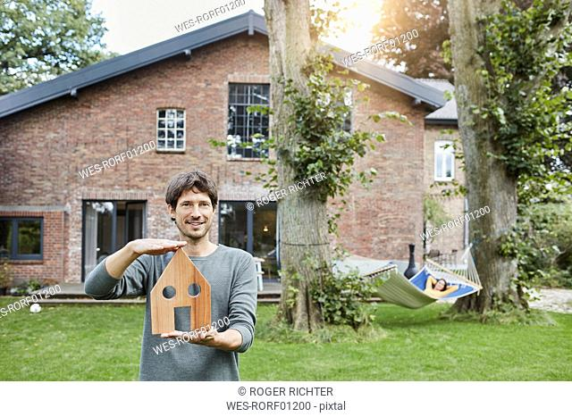 Portrait of man in garden of his home holding house model with woman in background lying in hammock