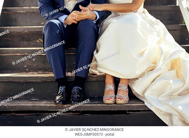 Bridal couple sitting on stairs outdoors, partial view