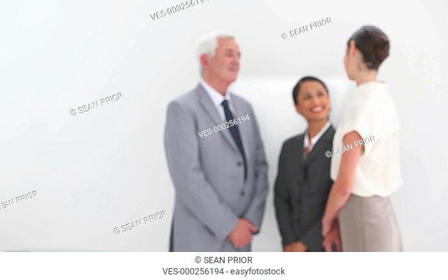Junge h?bsche Frau in Kost?m stellt sich von links kommend l?chelnd in den Vordergrund. Eine Gruppe steht im Hintergrund und unterh?lt sich