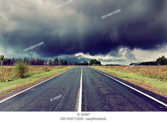 asphalt road and dark thunder clouds over it