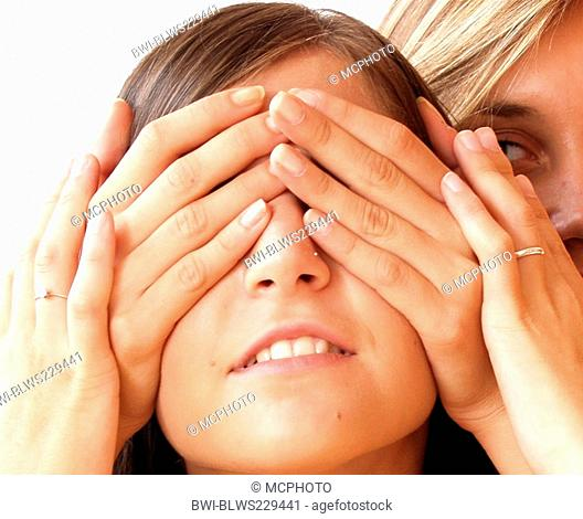 Woman covering the eyes of another woman from behind