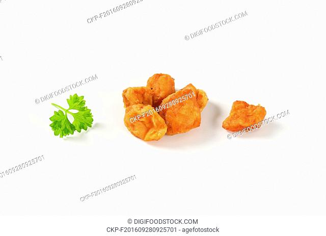 handful of pork scratchings on white background