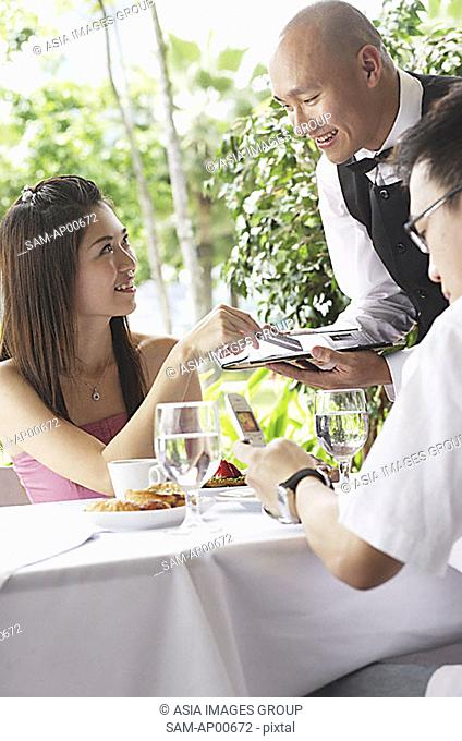 Couple in restaurant, woman making payment to waiter