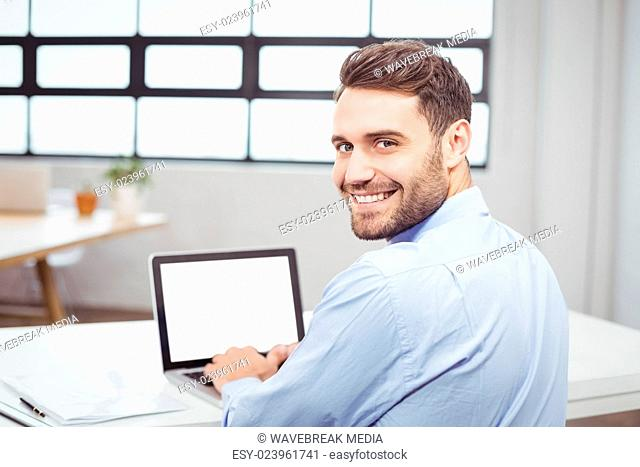 Portrait of happy businessman using laptop in office