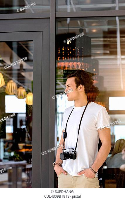 Photographer with camera around neck waiting by cafe entrance