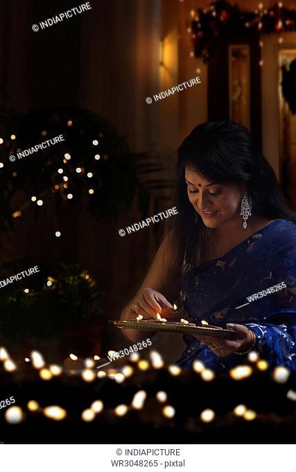 Beautiful indian woman in traditional sari arranging oil lamp during diwali festival