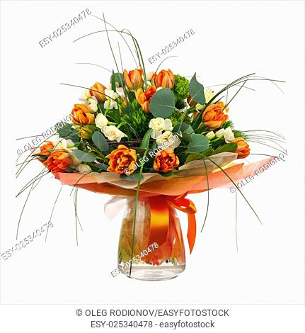 Bouquet of narcissus, tulips and other flowers in glass vase isolated on white background. Closeup