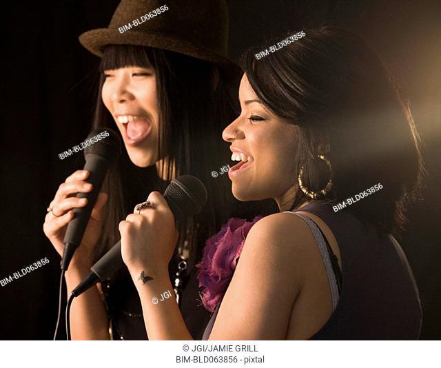 Multi-ethnic friends singing karaoke
