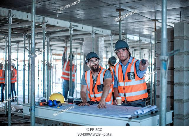 Site foreman and builder pointing from blueprint in construction site