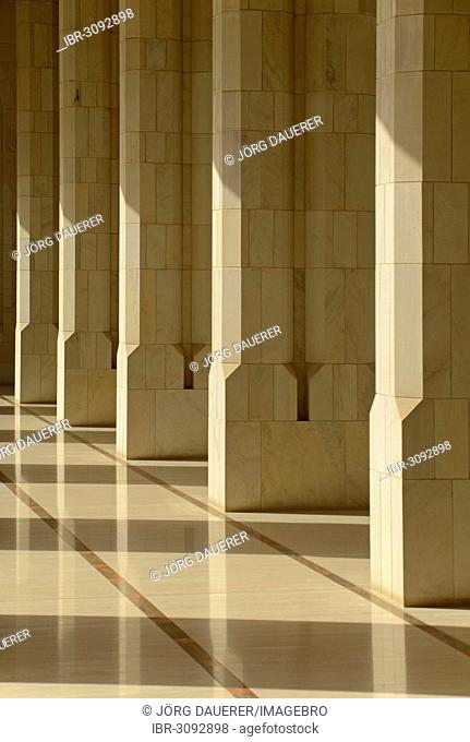 The columns and arches of an archway inside Sultan Qaboos Grand Mosque