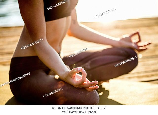 Close-up of woman practicing yoga on jetty at a lake
