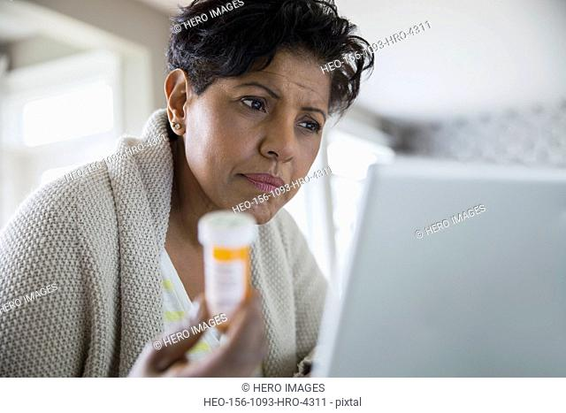 Concerned woman holding prescription bottle at laptop