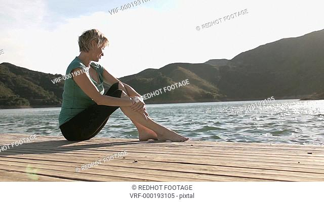 Dolly shot of woman sitting and relaxing on jetty at lakeside