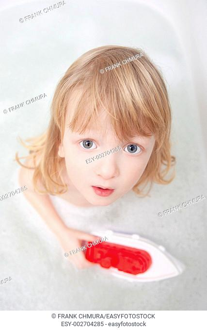 boy with long blond hair playing with plastic boat in bathtub