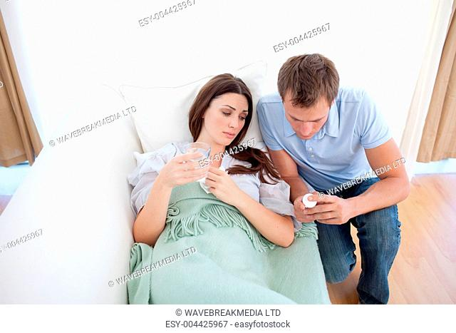 Man giving pills to his sick wife