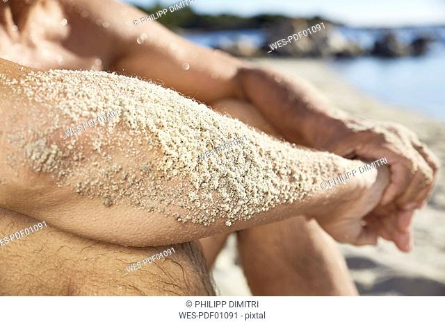 Sandy forearm of man relaxing on the beach, close-up