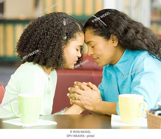 Hispanic mother and daughter praying in coffee shop
