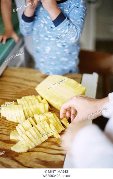 Woman cutting a fresh pineapple for her children