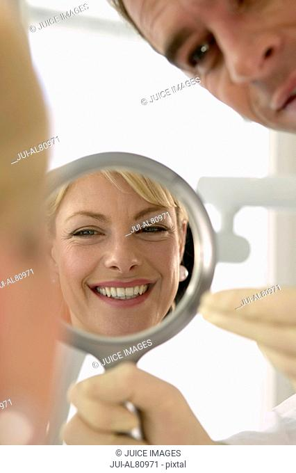 Reflection of woman smiling in mirror with dentist