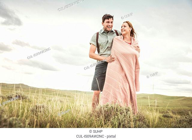 Happy young woman wrapped in blanket with boyfriend in landscape, Cody, Wyoming, USA