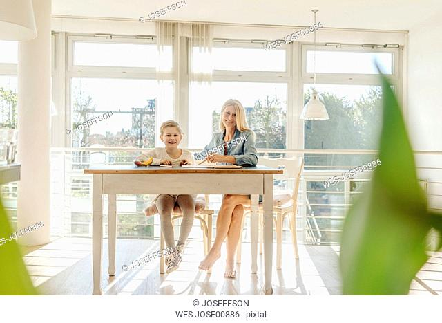 Mature woman and girl at home drawing together